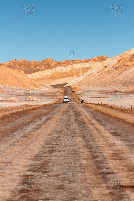 Vehicle and people on a dirt road in the Valley of the Moon in the Atacama desert, Chile