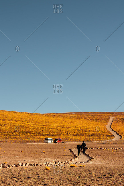 Couple walking on a dirt road in the Antofagasta Region, Chile