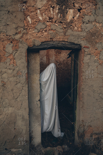 Scary ghost looking out doorway of an abandoned house