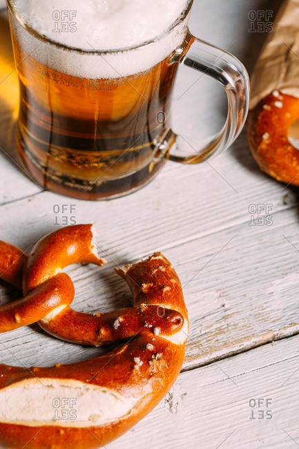 Glass of a beer and pretzel missing a bite on wooden white table