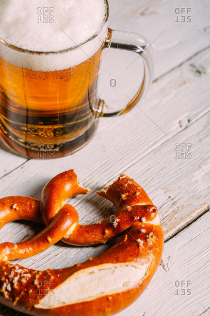 Pretzel missing a bite with a glass of beer on wooden white table