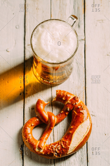 Overhead view of beer and pretzel missing a bite on wooden white table