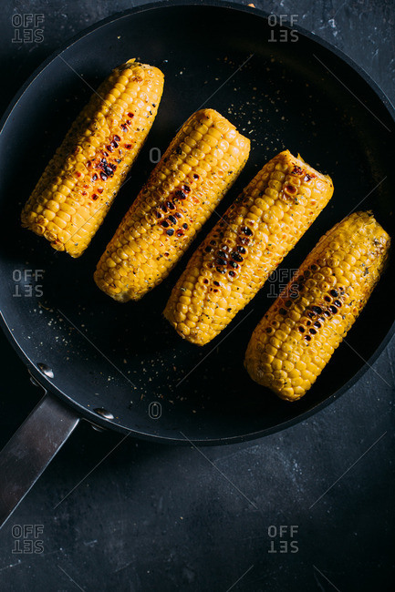 Overhead view of grilled corn with spicy sauce in a frying pan