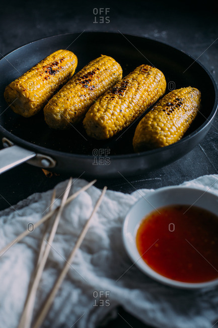 Close up of grilled corn with spicy sauce in a frying pan with red sauce