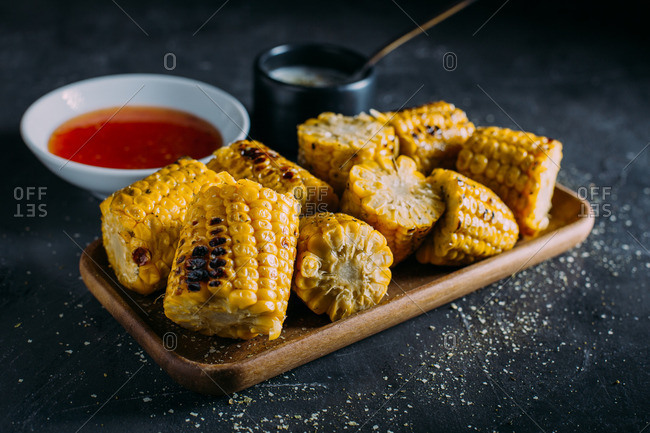 Close up of grilled corn with spicy sauce and mayo on a wooden tray
