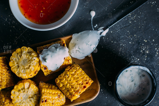 Overhead view of grilled corn with mayo on a wooden tray