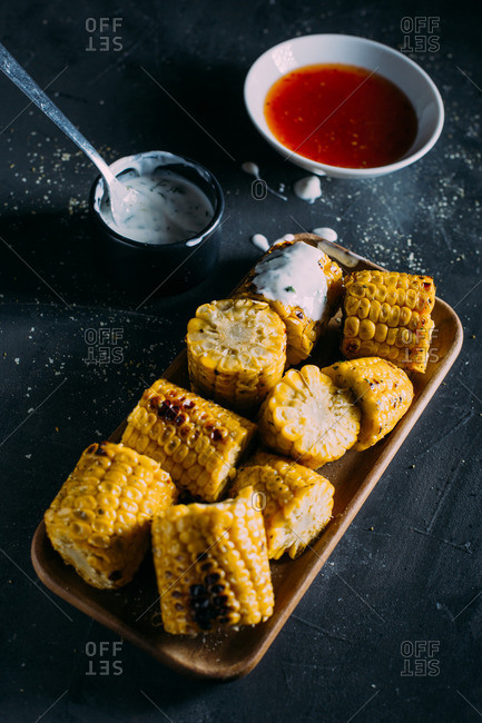 Grilled corn with mayo on a wooden tray and red sauce