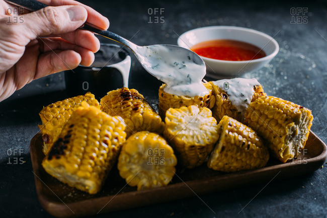 Person topping grilled corn with on a wooden tray