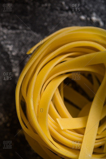 Close up of raw tagliatelle noodles on dark table