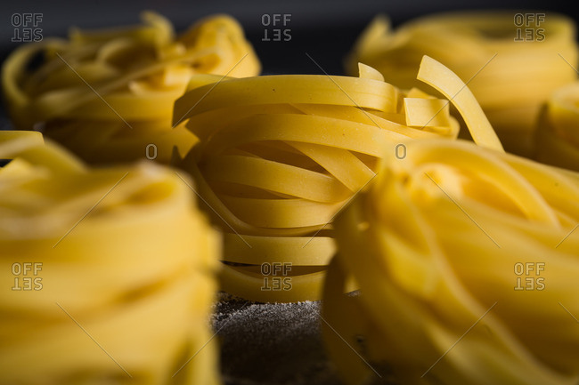 Close up of tagliatelle noodles on dark table