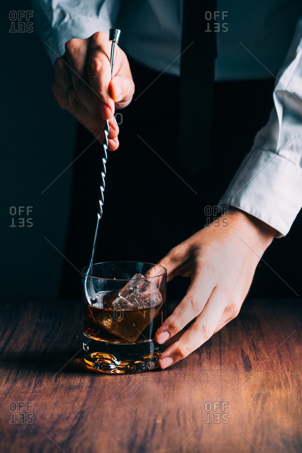 Man stirring a glass of whiskey on a wooden table