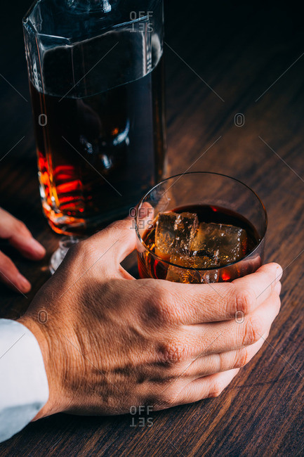 Man holding a glass of whiskey on a wooden table