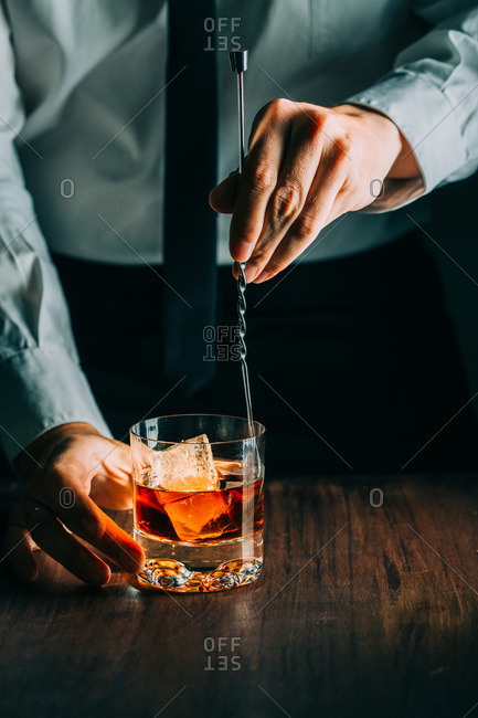 Glass of whiskey on a wooden table and with a man hand holding a mixing spoon
