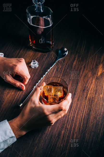 Man holding a glass of whiskey on a wooden table by a bottle and stirring spoon