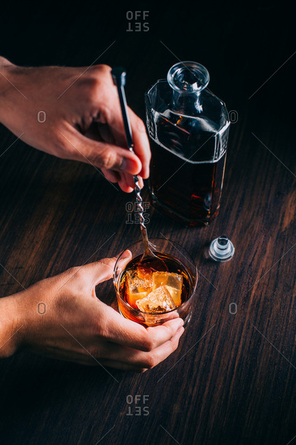 Hand stirring a glass of whiskey on a wooden table by a bottle