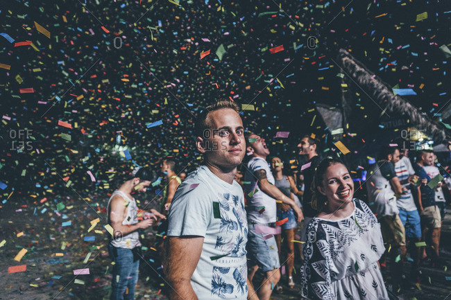 July 23, 2016: Confetti flying in the air around people at a night party