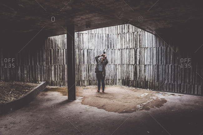 Photographer standing in abandoned building and shooting upwards with her camera