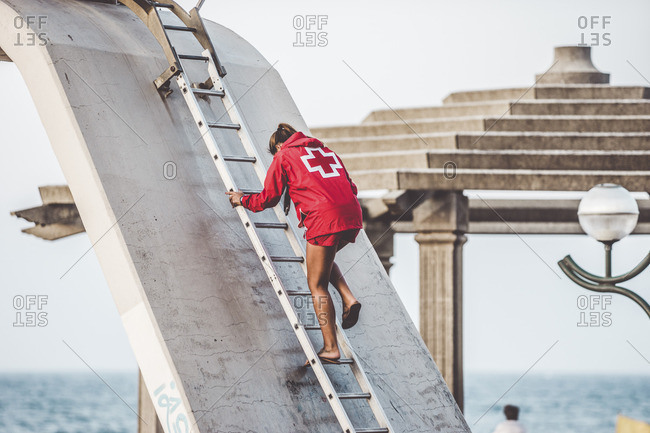 Back view of young girl lifeguard in red suit descending the ladder on a beach
