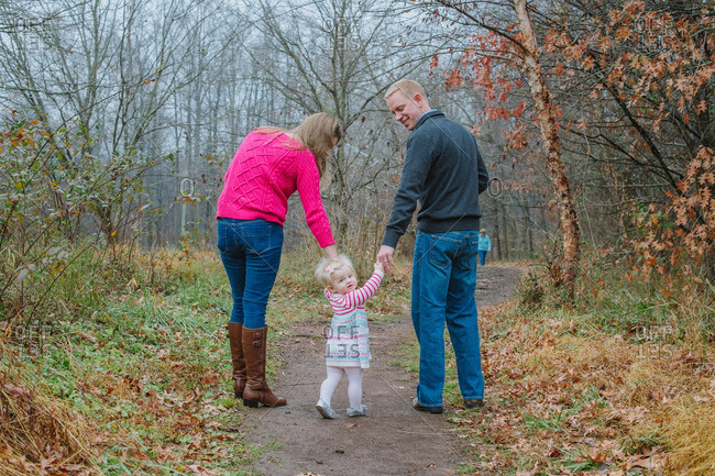 Toddler walking rural path with parents