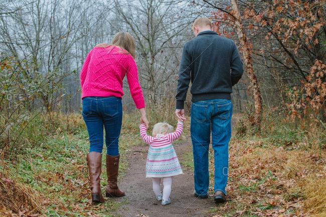 Parents walking toddler girl on rural path