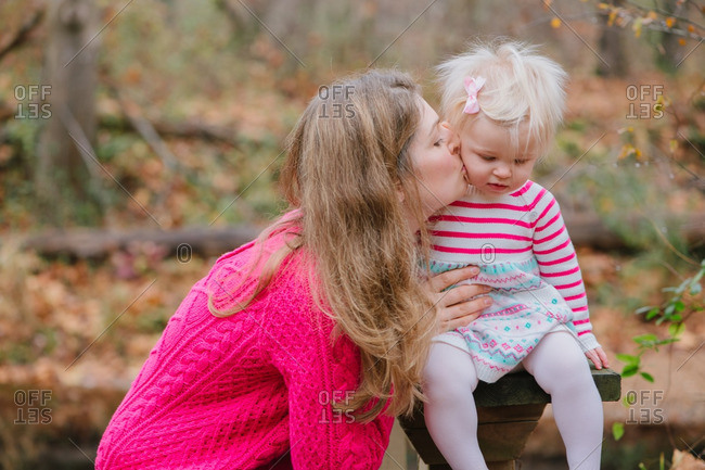 Mom kissing blonde toddler in countryside