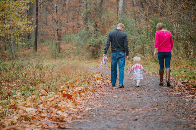 Parents walking with toddler on rural path