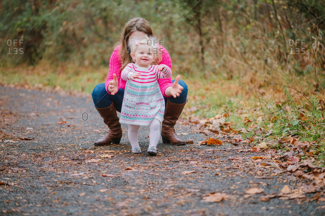 Toddler walking from woman on rural path