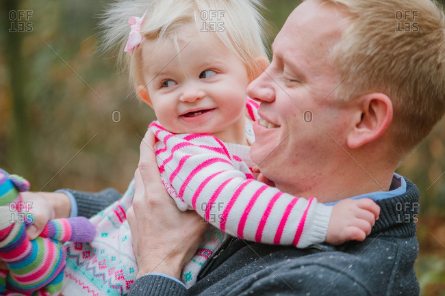 Dad holding blonde girl in wooded setting