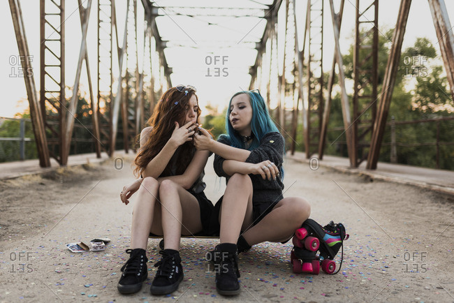 Teen punk girl sitting on skateboard on a bridge lighting her friend's cigarette