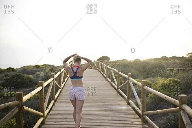 Woman tying hair back on a wooden boardwalk before a jog