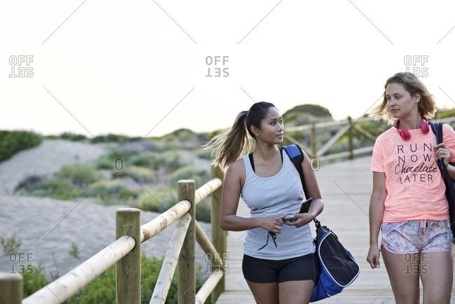 Friends walking on a wooden boardwalk before a jog