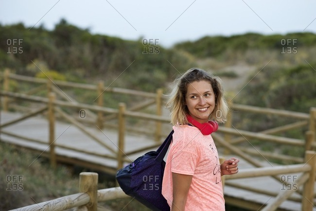 Woman wearing athletic clothing and headphones looking back as she walks away