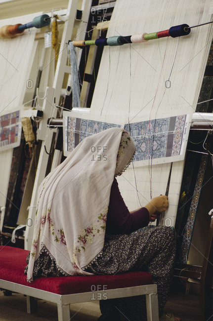 Turkish woman making traditional carpet on loom, Cappadocia, Turkey