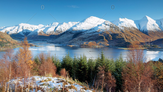 The snow covered peaks of the Kintail mountain range and autumn colored trees from the viewpoint at Mam Ratagan on the road to Glenelg, Skye and Lochalsh