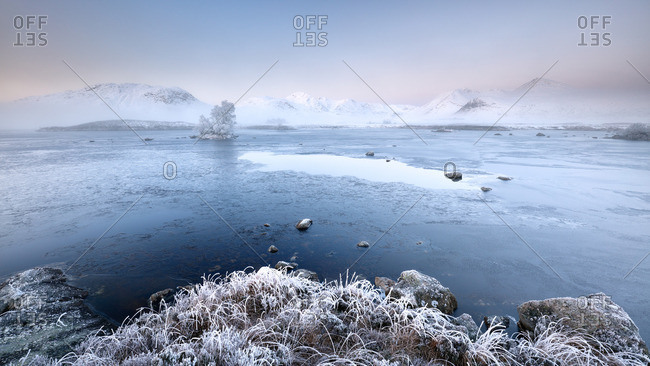 Sunrise on a snow, mist, ice and frost covered landscape at lochan na achlaise near Glencoe in the Scottish highlands
