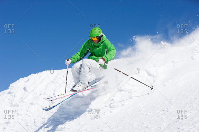 Man in green skiing off piste