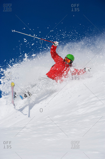 Man in red falling mid carve off-piste