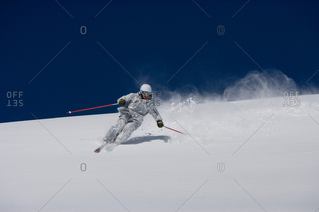 Man in white and grey camo suit off-piste