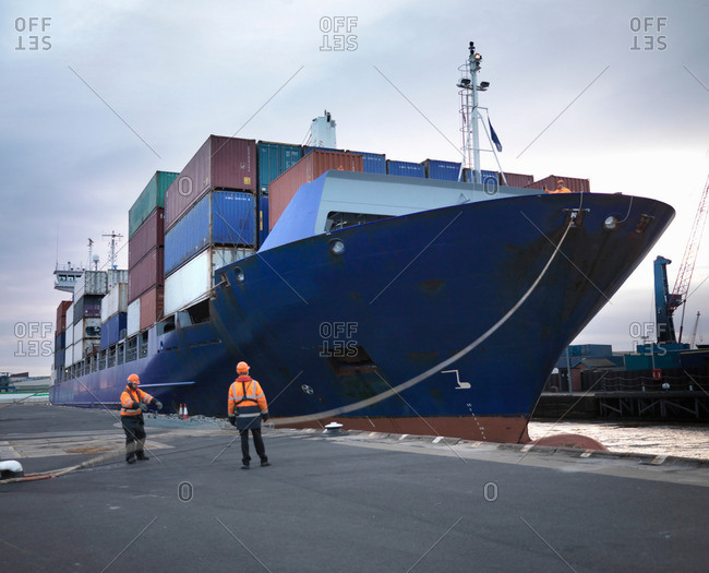 Port Workers With Loaded Ship At Port