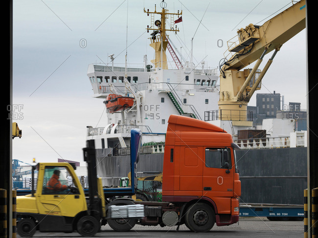 Port Worker In Forklift With Ship