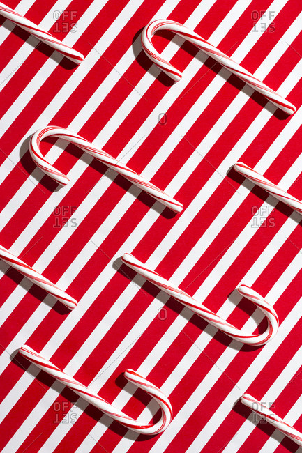 Holiday-themed still life image of candy cane on top of red and white background