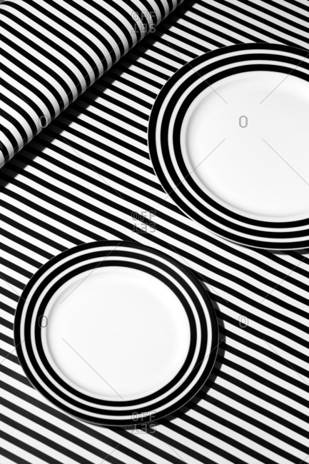 Still life image of plates on top of black and white striped background