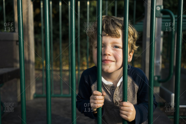 Boy leaning against bars on a playground smiling