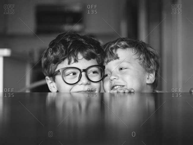 Two brothers resting heads together at the edge of a table