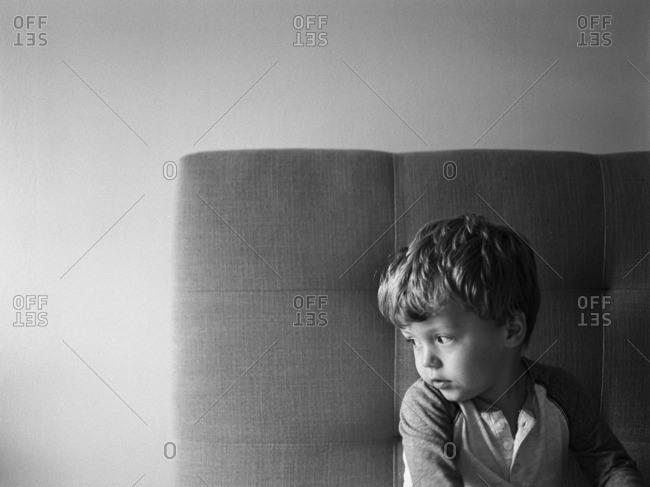 Little boy sitting on a tufted sofa