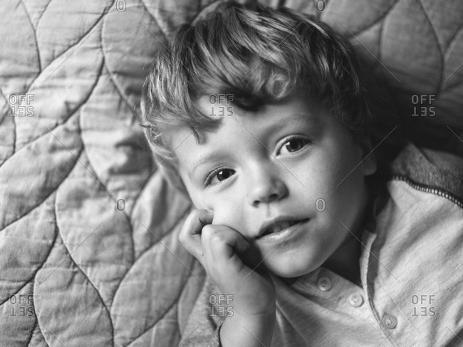 Toddler boy lying on a quilted blanket