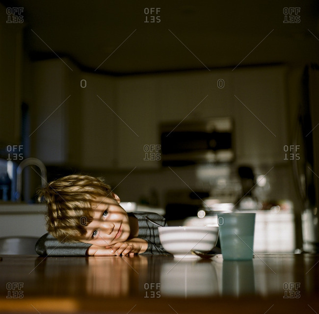 Little boy resting his head on a dining table next to a bowl and cup