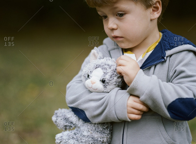 Little boy carrying a stuffed cat toy