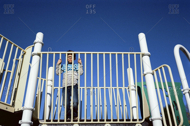 Little boy standing on playground equipment looking through the bars