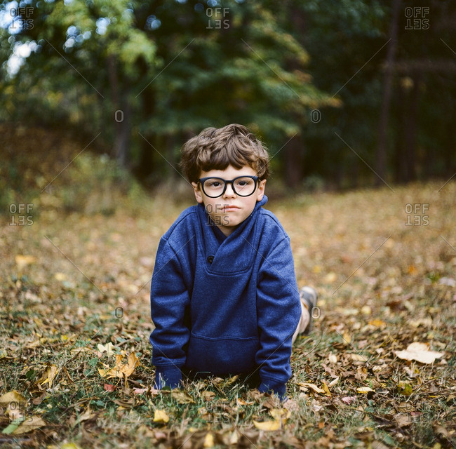 Boy in glasses and sweatshirt lying on autumn leaves